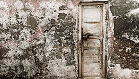Παλαιά ξύλινη πόρτα σε έναν παλαιό ραγισμένο παλαιό τοίχο Στοκ Εικόνες