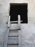 Παλαιά ξύλινη σκάλα στο παράθυρο πέρα από τον τοίχο στοκ εικόνες