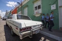 Παλαιά παιδιά αυτοκινήτων και σχολείων που περπατούν πίσω από το σχολείο στην οδό ο Στοκ φωτογραφία με δικαίωμα ελεύθερης χρήσης