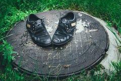 Παλαιά παπούτσια ατόμων ` s Εγκαταλειμμένος στην οδό μετά από μια βροχή Φορεμένος και Στοκ φωτογραφία με δικαίωμα ελεύθερης χρήσης