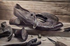 Παλαιά παπούτσια και εργαλεία επισκευής στον ξύλινο πίνακα Στοκ Φωτογραφίες