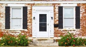 Παλαιά παράθυρα μπροστινών πορτών και κρεβάτι λουλουδιών Στοκ φωτογραφία με δικαίωμα ελεύθερης χρήσης