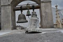 Παλαιά παραδοσιακά χρησιμοποιημένα κουδούνια εκκλησιών που κρεμούν μαζί στο ξύλινο ραβδί Στοκ εικόνες με δικαίωμα ελεύθερης χρήσης