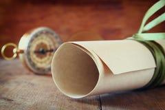 Παλαιά περγαμηνή και παλαιά πυξίδα στον ξύλινο πίνακα Στοκ Φωτογραφία