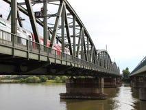 Παλαιά πράσινη γέφυρα σιδηροδρόμου μετάλλων με το κόκκινο τραίνο που διασχίζει τον ποταμό Στοκ Εικόνα