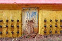 Παλαιά πόρτα και κίτρινος τοίχος ενός αρχαίου ινδού ναού με τις ελαιολυχνίες Στοκ Φωτογραφία