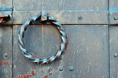 Παλαιά πόρτα μετάλλων grunge με τα καρφιά και στριμμένη σκουριασμένη λαβή πορτών υπό μορφή δαχτυλιδιού Στοκ Εικόνες
