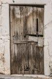 Παλαιά πόρτα ξυλείας στο γρατζουνισμένο τοίχο Στοκ Φωτογραφίες