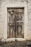 Παλαιά πόρτα ξυλείας στο γρατζουνισμένο τοίχο Στοκ Εικόνες