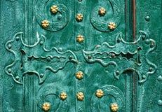 Παλαιά πόρτα σιδήρου, που σφυρηλατείται και που χρωματίζεται στο πράσινο χρώμα με τα χρυσά λουλούδια για το υπόβαθρο, εκλεκτής πο Στοκ φωτογραφία με δικαίωμα ελεύθερης χρήσης