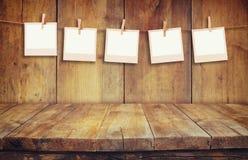 Παλαιά πλαίσια φωτογραφιών polaroid που σε ένα σχοινί με το ξύλινο υπόβαθρο Στοκ Εικόνα