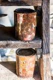 Παλαιά σκουριασμένα δοχεία, που ξεχνιούνται στα παλαιά ξύλινα σκαλοπάτια Στοκ εικόνα με δικαίωμα ελεύθερης χρήσης