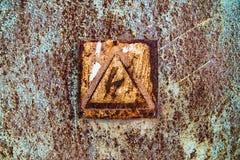 Παλαιά σκουριασμένη επιφάνεια κασσίτερου με το προειδοποιητικό σημάδι της υψηλής τάσης Στοκ Εικόνες