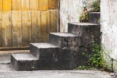 Παλαιά συγκεκριμένα σκαλοπάτια κοντά στον ξύλινο τοίχο στοκ φωτογραφίες με δικαίωμα ελεύθερης χρήσης