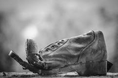 Παλαιά σχισμένη μπότα στο Μαύρο παραθύρων Στοκ Εικόνες