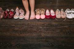 Παλαιά φορεμένα παπούτσια μωρών (παιδί, παιδί) στο πάτωμα σανδάλια, μπότες, s Στοκ Εικόνες