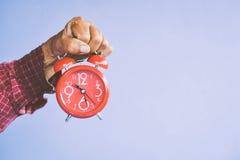 Παλαιά χέρια που κρατούν το κόκκινο ξυπνητήρι Στοκ Εικόνες
