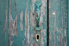 Παλαιά χρωματισμένη πόρτα με τη λαβή και την κλειδαρότρυπα Στοκ Φωτογραφία