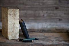 Παλαιές βιβλία και μάνδρα πηγών με το ξύλινο υπόβαθρο Στοκ Εικόνα