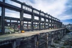 Παλαιές βιομηχανικές καταστροφές που χτίζουν - καταστροφές ναυπηγείων Agenna με το νεφελώδη ουρανό απογεύματος, πυροβολισμός στην Στοκ Εικόνες