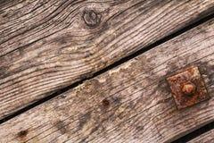 Παλαιές σάπιες σανίδες με τα σκουριασμένα καρφιά και τετραγωνικό πλυντήριο με το καρύδι βιδών Στοκ Εικόνες