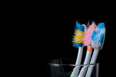 Παλαιές χρησιμοποιημένες οδοντόβουρτσες στο γυαλί στο μαύρο υπόβαθρο Στοκ φωτογραφία με δικαίωμα ελεύθερης χρήσης