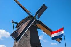 Παλαιοί ανεμόμυλος και σημαία, Zaanse Schans, Κάτω Χώρες Στοκ Εικόνα