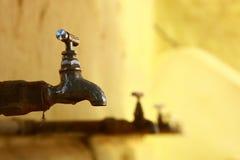Παλαιοί γερανοί για το νερό ενάντια στον κίτρινο τοίχο Στοκ φωτογραφία με δικαίωμα ελεύθερης χρήσης