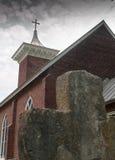 Παλαιοί σταυρός πετρών και εκκλησία τούβλου που στηρίζεται στη νεφελώδη ημέρα Στοκ εικόνες με δικαίωμα ελεύθερης χρήσης