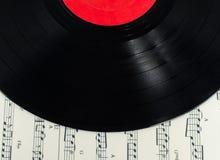 Παλαιός δίσκος σε μουσικό χαρτί σημειώσεων Στοκ εικόνες με δικαίωμα ελεύθερης χρήσης