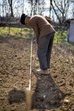 Παλαιός αγρότης με την εργασία καπέλων του Αστραχάν Στοκ εικόνες με δικαίωμα ελεύθερης χρήσης