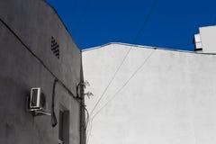 Παλαιός γκρίζος τοίχος οικοδόμησης στόκων στο υπόβαθρο του μπλε ουρανού, περίληψη πόλεων Στοκ εικόνα με δικαίωμα ελεύθερης χρήσης
