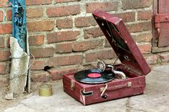 Παλαιός εκλεκτής ποιότητας gramophone φορέας σε μια κόκκινη περίπτωση που εγκαταλείπεται έξω Στοκ Εικόνα