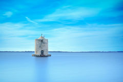 Παλαιός ισπανικός ανεμόμυλος σε μια μπλε λιμνοθάλασσα. Orbetello, Argentario, Ιταλία. Στοκ Φωτογραφία