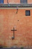 Παλαιός μεσαιωνικός ξύλινος δρύινος καθολικός σταυρός στον επικονιασμένο κόκκινο τοίχο Στοκ εικόνες με δικαίωμα ελεύθερης χρήσης