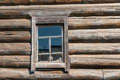 Παλαιός ξύλινος τοίχος σπιτιών κούτσουρων με το παράθυρο που γέρνουν σε μια πλευρά Στοκ Φωτογραφία
