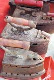 Παλαιός σίδηρος που τακτοποιείται σε ένα κόκκινο υπόβαθρο Στοκ Φωτογραφίες