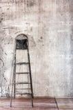 Παλαιός συμπαγής τοίχος στην επισκευή του δωματίου με το βρώμικο πάτωμα και steplad Στοκ Εικόνα