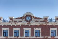 Παλαιός τουβλότοιχος με γεμισμένα τα τούβλο παράθυρα και παλαιό ρολόι Στοκ Εικόνες