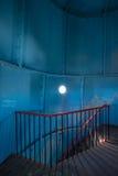 Παλαιός φάρος στο εσωτερικό Κόκκινα σπειροειδή σκαλοπάτια σιδήρου, στρογγυλό παράθυρο και μπλε τοίχος Στοκ εικόνα με δικαίωμα ελεύθερης χρήσης
