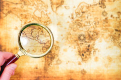 Παλαιός χάρτης και ενίσχυση - γυαλί σε ένα χέρι Στοκ Εικόνες
