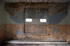 Παλαιός χρωματισμένος τοίχος στο εγκαταλειμμένο κτήριο με τα μικρά παράθυρα Στοκ Φωτογραφία