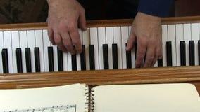 Παλαιότερα αρσενικά χέρια που παίζουν την κορυφή πιάνων κάτω από την άποψη απόθεμα βίντεο