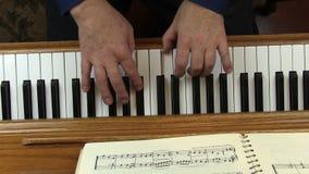Παλαιότερα αρσενικά χέρια που παίζουν την κορυφή πιάνων κάτω από την άποψη φιλμ μικρού μήκους