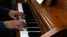 Παλαιότερα αρσενικά χέρια που παίζουν το πιάνο που αντιμετωπίζεται από την πλευρά φιλμ μικρού μήκους