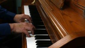 Παλαιότερα αρσενικά χέρια που παίζουν το όρθιο πιάνο από την πλευρά φιλμ μικρού μήκους