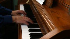 Παλαιότερα αρσενικά χέρια που παίζουν το όρθιο πιάνο από την πλευρά απόθεμα βίντεο