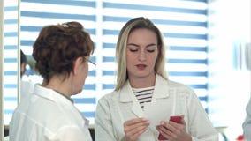 Παλαιότερη νοσοκόμα που φέρνει το ιατρικό έγγραφο στη νέους νοσοκόμα και στον αρσενικό γιατρό φιλμ μικρού μήκους