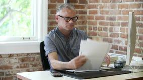 Παλαιότερος επιχειρηματίας που εργάζεται στο γραφείο στο στούντιο σχεδίου απόθεμα βίντεο