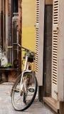 Παλαιό άσπρο ποδήλατο που κλίνει ενάντια στον τοίχο στο ιστορικό κέντρο Στοκ Εικόνες